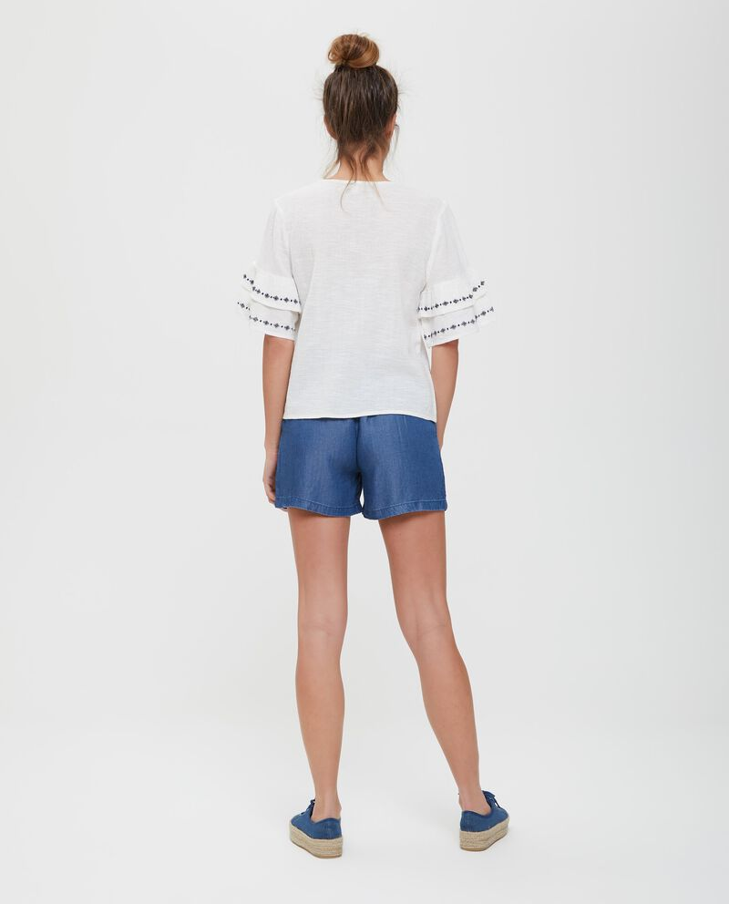Blusa in cotone con ricami e pon pon